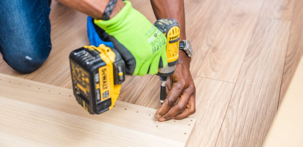 When to Call in the Professionals for Home Repair | Powell Realtors (showing a man with drill and lumber)