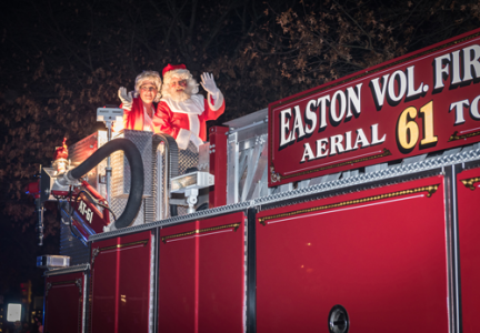 Santa and Mrs. Claus waiving hello from a firetruck in downtown Easton, MD